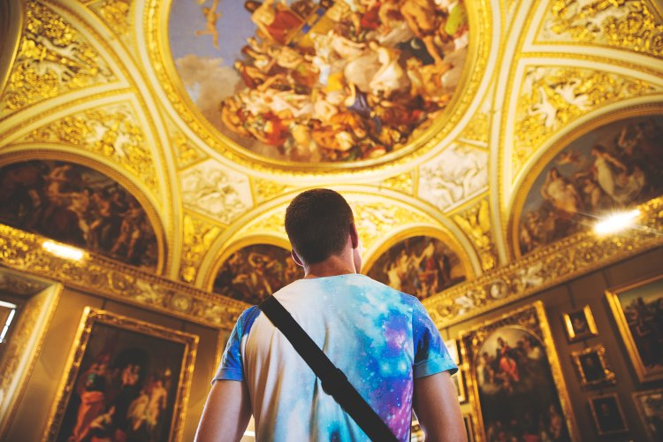 A young man in a colorful galactic t-shirt gazes up at an ornate gilt and fresco ceiling depicting paradise, with Jesus Christ seated on a throne surrounded by a joyful crowd.